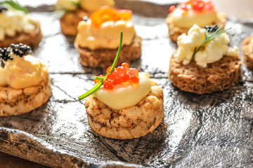 Delicious canapes with black and red caviar on plate, closeup