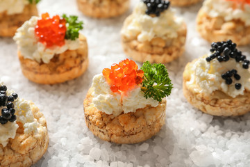Delicious canapes with black and red caviar on sea salt