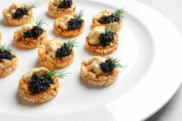 Tasty black caviar appetizer on plate