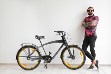 Portrait of handsome hipster with bicycle near white wall