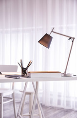 Comfortable workplace with modern lamp on table