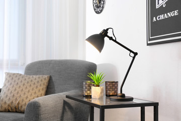 Living room interior with modern lamp on table and comfortable armchair