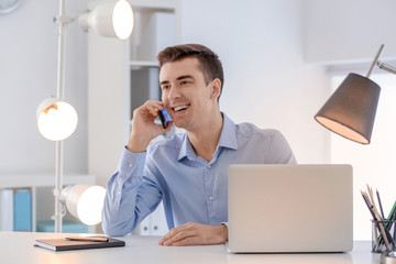 Young man talking on phone at table indoors