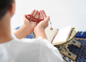 Young Muslim man with beads praying over Koran on floor