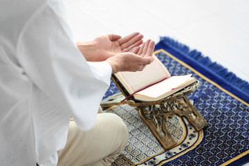 Young Muslim man praying over Koran on floor
