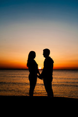 Silhouette of couple facing each other on the beach at sunrise.