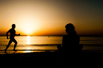 Silhouette young woman practicing yoga on the beach at sunrise.