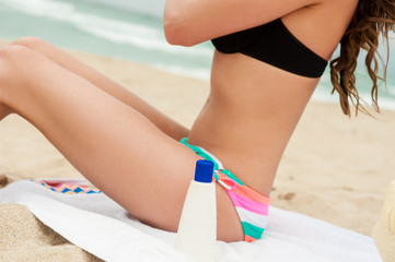 Woman applying sun protection lotion. Bottle of sun protection lotion and flip flops. Close-up, no face!