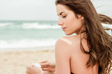Woman at the beach with a on bandage her upper back.