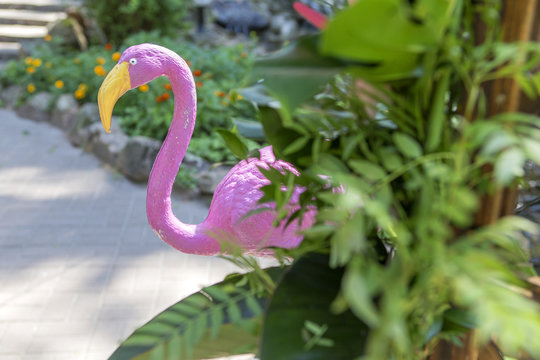 Pink fake flamingo wedding decoration with anthurium flowers and monstera leafs, colorful balloons on arch. Meadow in green garden, summer daylight