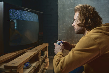 Side view interested bearded male typing in joystick while looking at display of retro television set. Funny entertainment concept