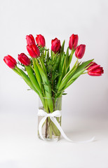 Fotobehang Tulp Bouquet of red tulips in vase white satin ribbon isolated.