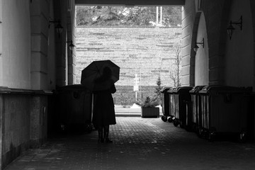 Woman under an umbrella in a dark arch