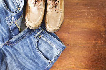 Close up of jeans pants and men's shoes on wooden background