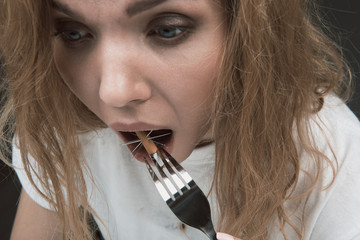 Close up of female stunned face cramming into mouth cigarette pierced with needles. Isolated on background