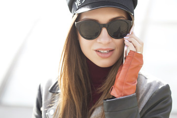 Brunette young caucasian woman in casual jacket (coat), jeans and sunglasses walking european city streets, smiling happily talking on a phone. Lifestyle portrait indoors. Copy space