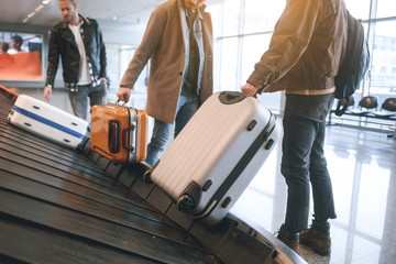 Wall Mural - Low angle male friends putting luggages while standing in airport. Journey concept