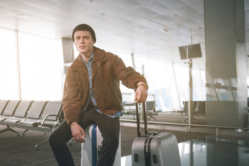 Portrait of weariful young man sitting on luggage while looking in camera in airport. Anticipation concept