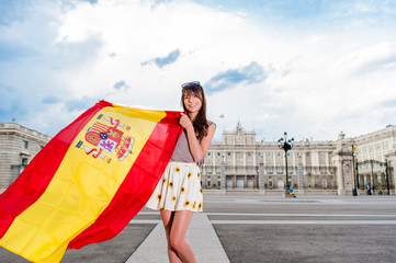 Young woman in front of Palacio de Oriente - the Royal Palace of Madrid, holding a flag