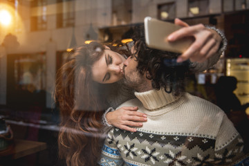 Affectionate young man and woman are kissing in lips with love. Girl is photographing them on mobile phone camera
