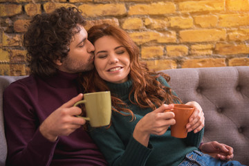 Portrait of excited young woman enjoying gentle kiss of her boyfriend. She is smiling with closed eyes. Couple is holding cups of coffee while sitting on couch