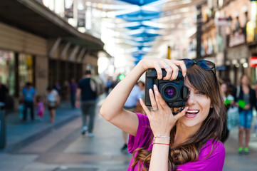 Young woman tourist holding a photo camera and taking picture in Plaza del Sol square, Madrid, Spain.