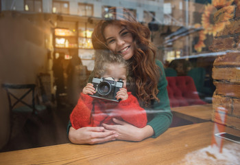 Happy family is spending time together in cozy cafeteria. Girl is photographing street over the window while woman is hugging her and smiling