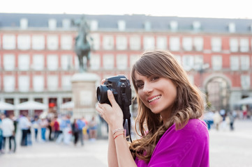 Young woman tourist holding a photo camera and taking picture in Plaza Mayor square, Madrid, Spain. Tourist attraction, statue of Felipe III in the background.