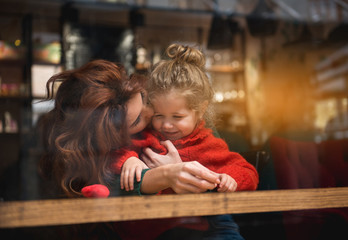 Cheerful woman is kissing her little daughter with love. She is cuddling the smiling girl while sitting at table in cafe