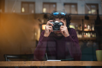 Portrait of young man using camera while sitting at table in cafeteria. He is looking outside the window with concentration