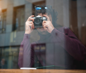 Serious male photographer taking photos on camera while sitting near window indoors