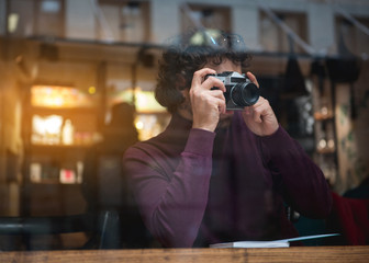 Calm young man is photographing street while sitting near window in cafe. Copy space