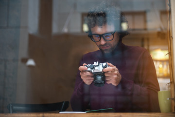 Portrait of concentrated young man looking at photos on digital device. He is having rest in cozy cafeteria. View from glass window. Copy space