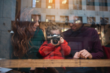 Portrait of happy family sitting at table near window. Excited little girl is photographing street by camera while father and mother smiling