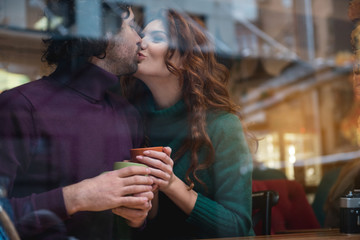 Excited woman kissing her husband in lips with love. She is smiling while holding mug of hot beverage. Lovers are sitting at table in cafeteria