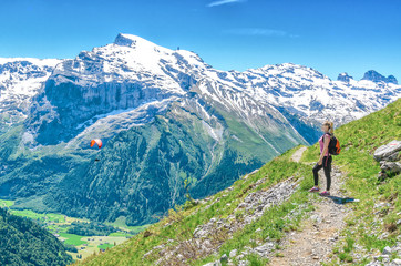 A girl with a red backpack admiring the scenery of the Alpine mountains. Landscape of the Swiss Alps, the Engelberg resort.