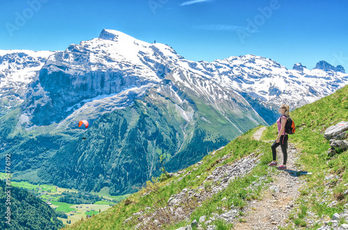 A girl with a red backpack admiring the scenery of the alpine a girl with a red backpack admiring the scenery of the alpine mountains landscape of voltagebd Images