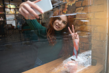 Portrait of cheerful girl photographing herself on mobile phone and smiling. She is showing peace sign not camera while resting in cozy cafeteria. View from glass window