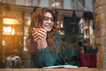 Portrait of happy young woman enjoying coffee in cozy cafeteria. She is keeping mug in both hands and laughing. Relaxation concept