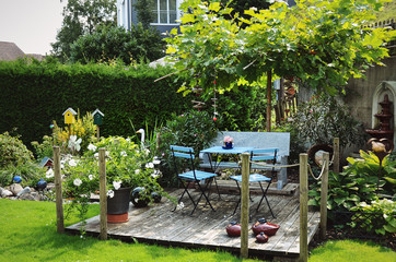 Garden terrace with table and chairs surrounded by blooming flowers and green plants