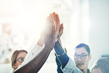 Diverse group of colleagues high fiving together in an office