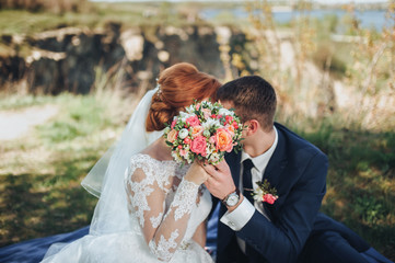 The bride and the groom are hiding behind a wedding bouquet. Kiss of the newlyweds. Picnic in the summer park.