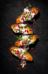 Baked sweet potatoes with garlic mint yogurt sauce sprinkled with pomegranate seeds and fresh mint leaves on a black background, top view