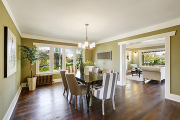 Light olive dining room features a wood carved dining table.