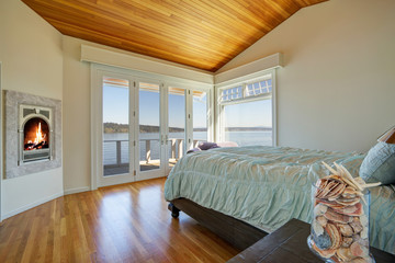 Light spacious bedroom with vaulted plank ceiling.