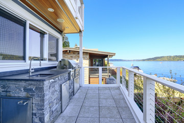 Large covered deck with built-in barbecue overlooking the lake