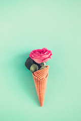 Creative minimalism still life on pastel turquoise colored background. Waffle cone with rose flower and eucalyptus from above. Copy space for text, vertical
