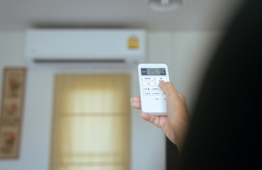 Hand using a remote control to activating temperature air conditioning
