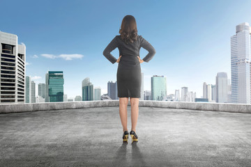 Back view of asian business woman with hand on her waist on the rooftop