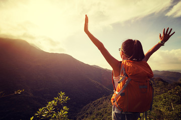 happy woman backpacker looking at the view  with arms outstretched on mountain top during sunrise Wall mural